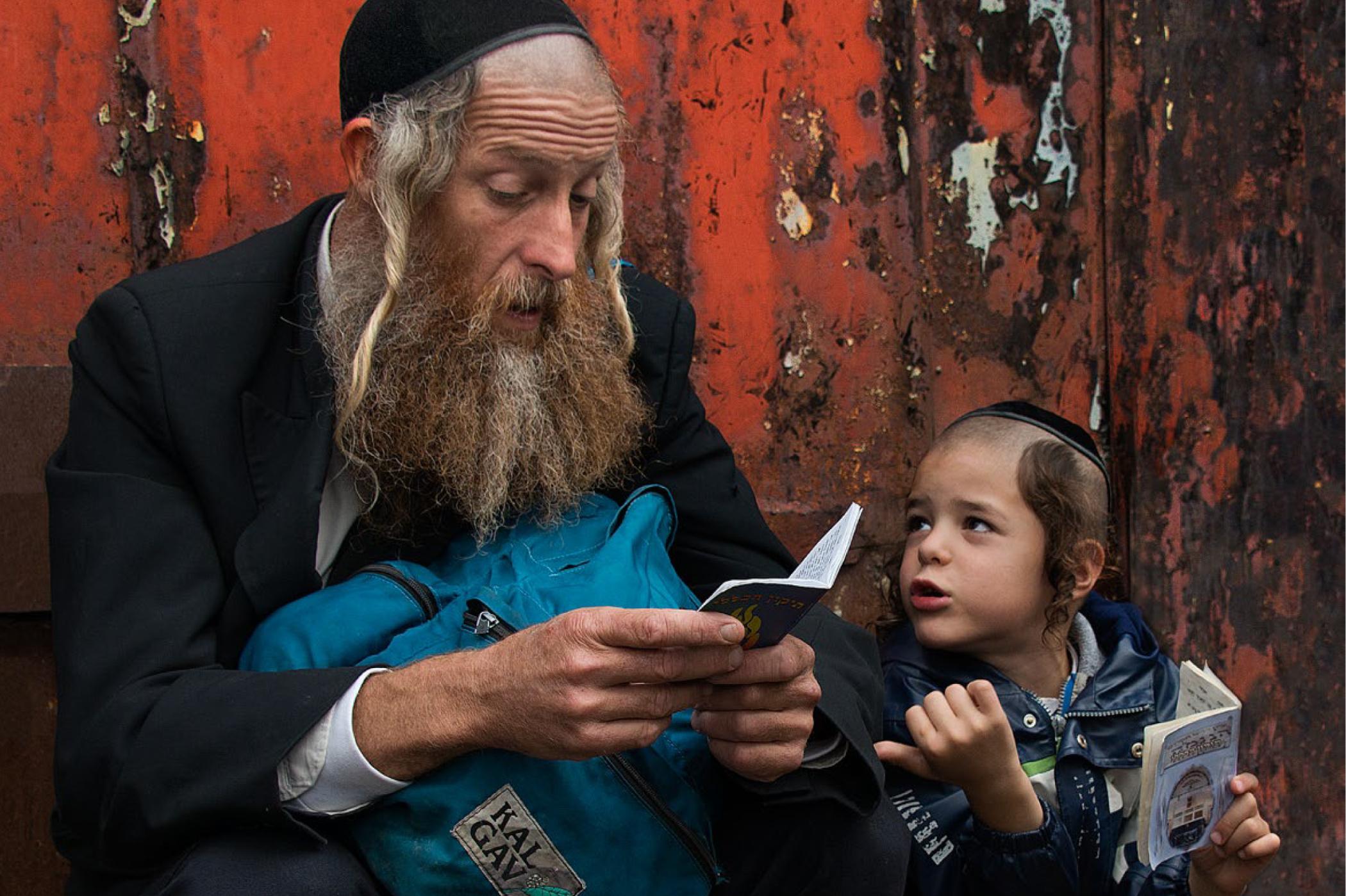 Z výstavy Svět, který měl zmizet: Chasidští poutníci v Umanu na Ukrajině. Otec se synem čtou žalmy u hrobky rabi Nachmana. Hasisic pilgrims in Uman in Ukraine