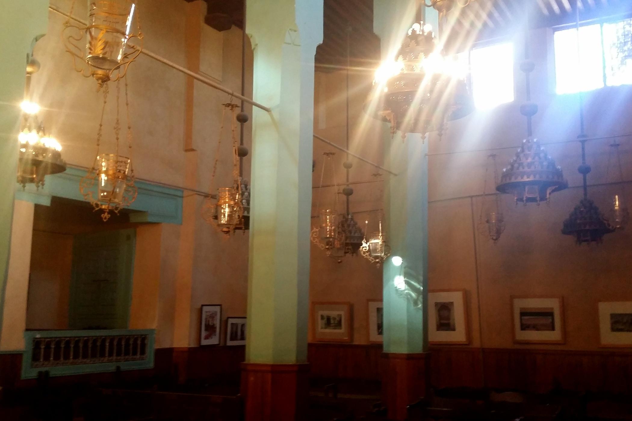 Sluneční paprsky se odrážejí od skleněných a bronzových svícnů lamp visících vedle zelených sloupů