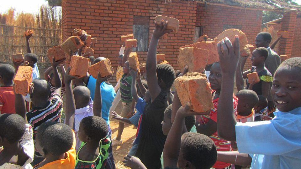 Humanitární mise v Malawi - Dětii i dospělí nesou cihly k základnímu kameni nemocnice