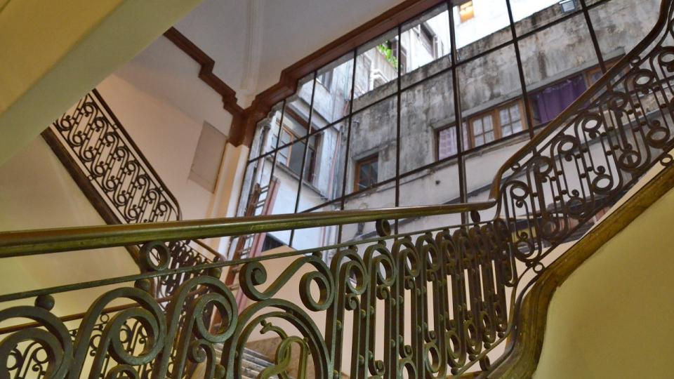 Jedno ze schodišť Paláce Salvo a průhled do málo pohledného vnitrobloku skrz léta rozbité okno