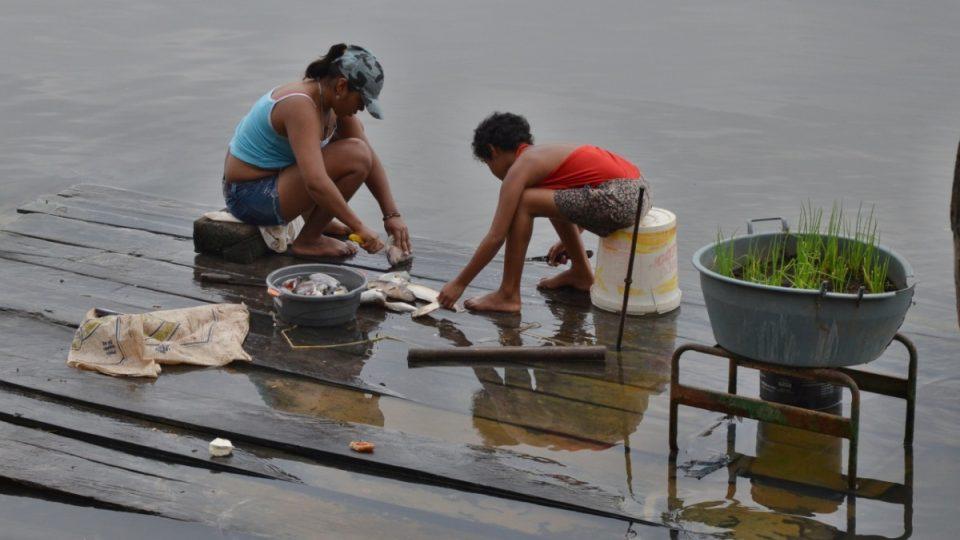 Dvě z mnoha dcer místní indiánské rodiny čistí ryby na břehu jezera