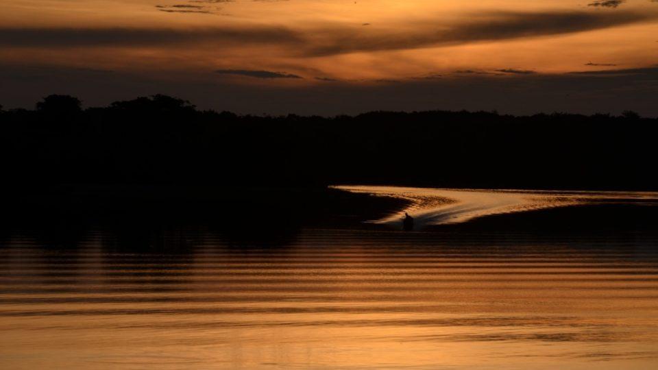 Loď přijíždějící k břehu v západu slunce