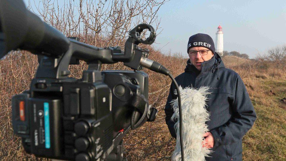Stefean Kreibohm před kamerou, v pozadí maják na ostrově Hiddensee