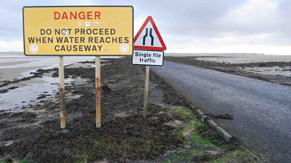 Informační tabule varuje, že vstupovat na silnici poté, co hladina vystoupá k náspu, není bezpečné
