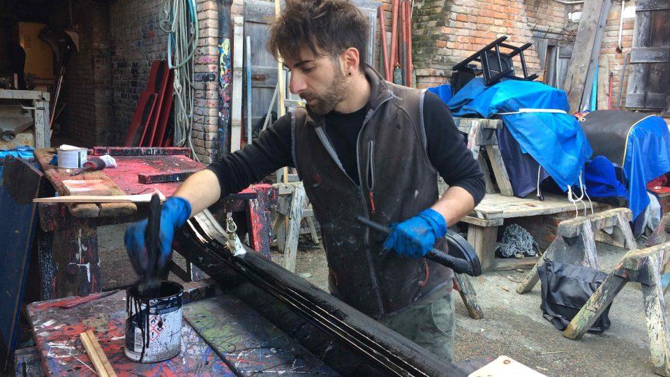 Diego lakuje opěrku gondoly jednou vrstvou černé barvy, boky třemi vrstvami
