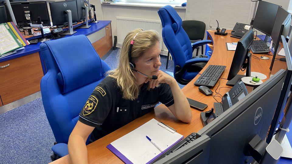Při práci sedí Jana Kumperová před několika monitory, na kterých má například mapu s polohami jednotek a přes vysílačku s nimi komunikuje.
