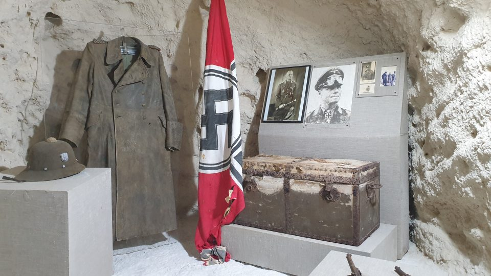 V celé jeskyni jsou prakticky jen tři vitríny. Hned v první je několik fotografií Erwina Rommela, je tu jeho osobní helma, kabát, dvě pistole