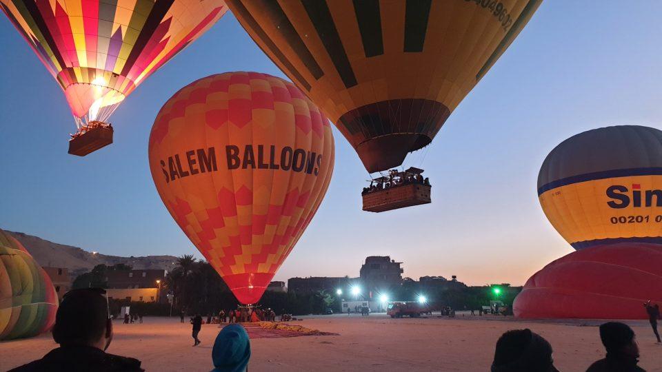 Ještě před východem slunce se asi dvacítka balonů postupně odlepuje od země