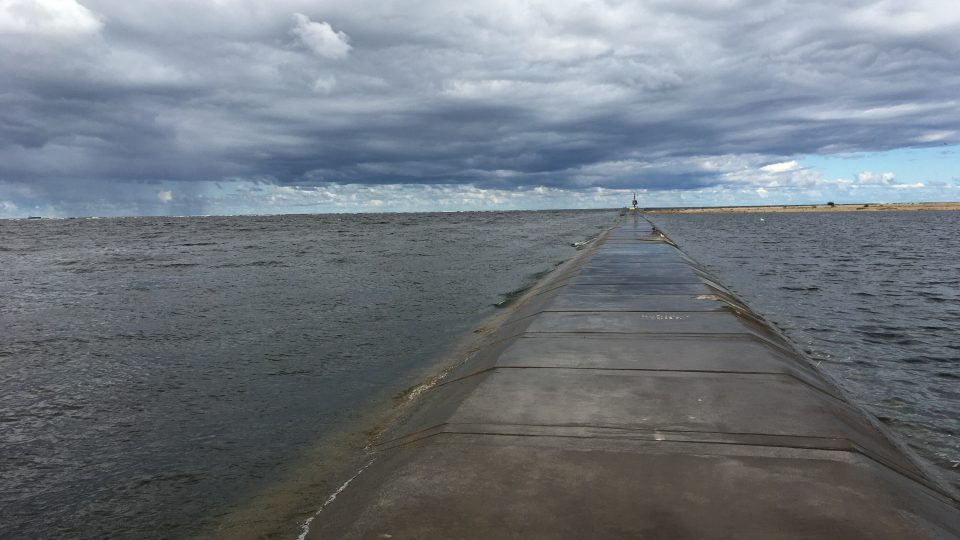 Betonové nábřeží zalévají vlny, takže je tu mokro. Cíl cesty leží nedaleko odtud