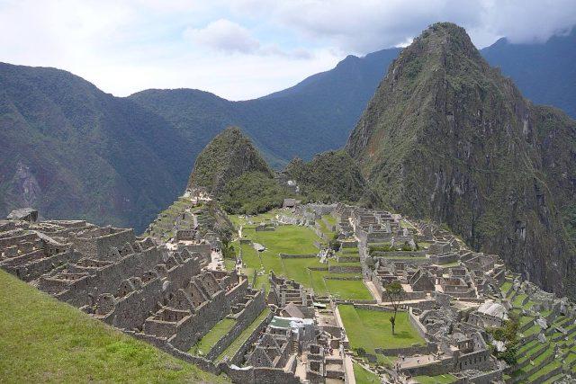 Machu Picchu (kečujsky Stará hora) s branou na inckou stezku za zády, uprostřed posvátné místo, v pozadí Wayna Picchu (kečujsky Mladá hora)