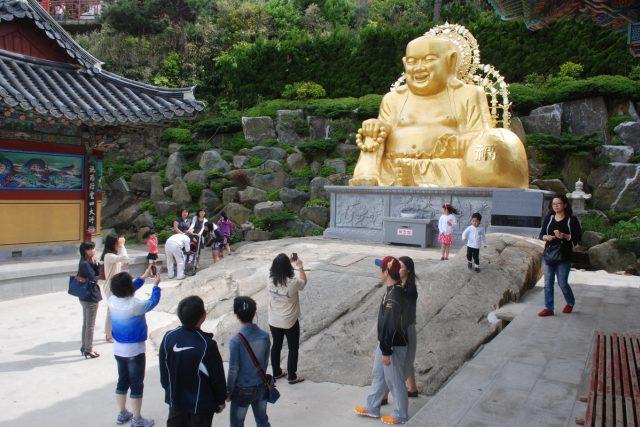 Zlatá socha Buddhy přitahuje objektivy fotoaparátů