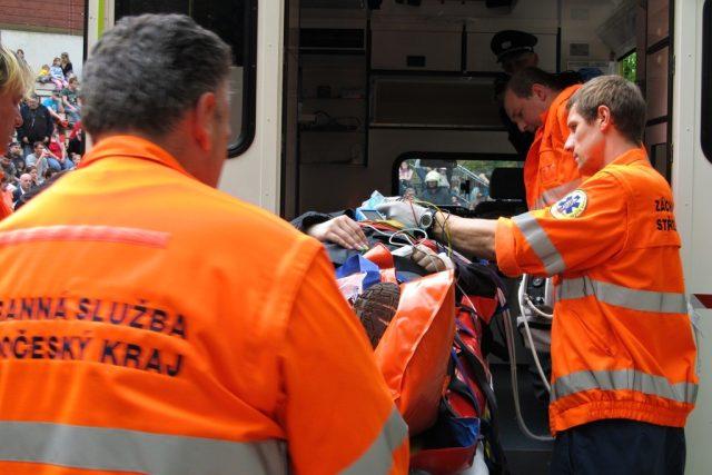 Záchranáři přepravují zraněnou osobu do sanitky