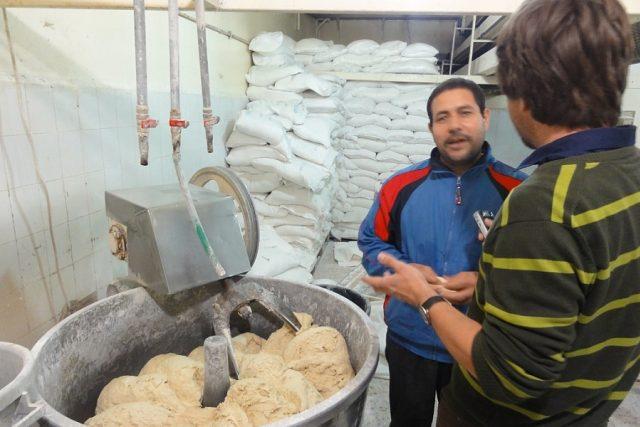 Egyptský pekař Fáris vysvětluje autorovi reportáže technologii hnětení arabské chlebové placky   foto: Štěpán Macháček,  Český rozhlas