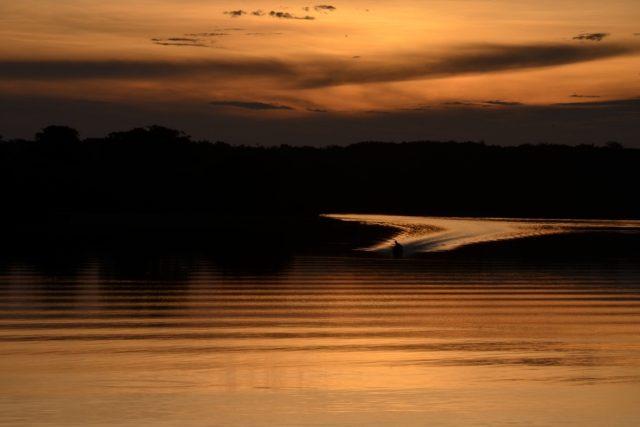 Loď přijíždějící k břehu v západu slunce | foto: David Koubek,  Český rozhlas
