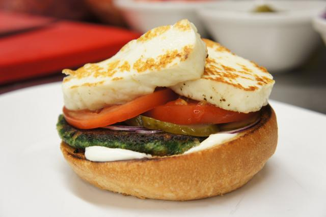 Mezi bulky dáme zeleninovou placku, sýr halloumi, plátek rajčete, cibuli a kyselou okurku