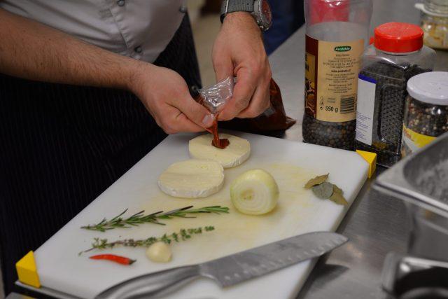 Hermelín rozkrojíme podélně na polovinu. Vnitřní stranu potřeme připravenou směsí z drceného stroužku česneku, chilli papriček a kečupu