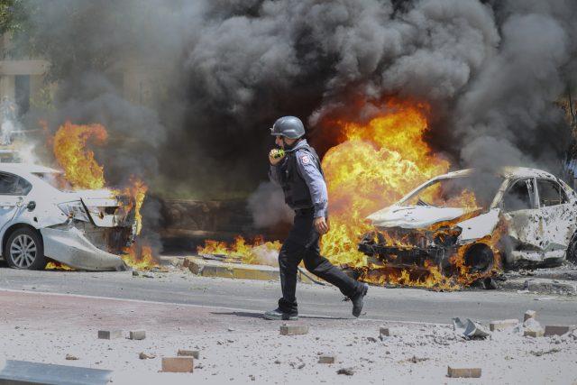 Hasič v jihoizraelském městě Aškelon kráčí vedle automobilů zasažených raketou vystřelenou z pásma Gazy | foto: Ariel Schalit,  ČTK/AP