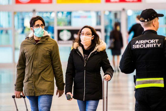 Ženy s rouškami na letišti