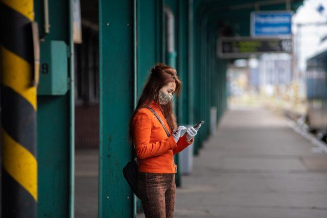 Mladá žena v roušce čeká v Pardubicích na vlak