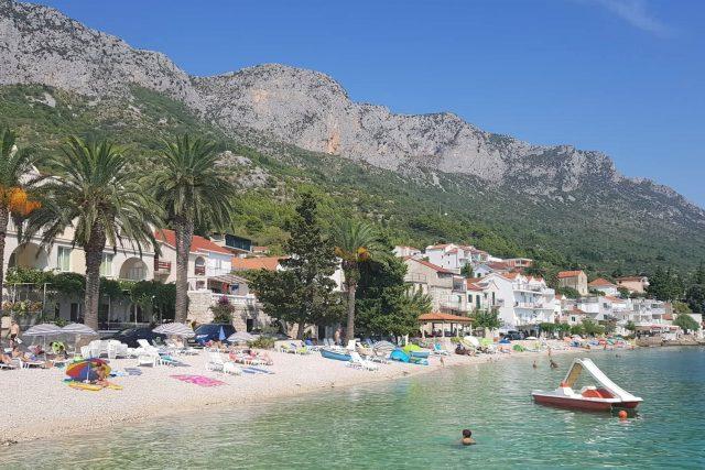 Chorvatsko, moře, vesnice Brist, Makarská riviéra, dovolená, koupání, pláž, léto, opalování, lehátka, slunečníky, turistické letovisko, cestování, pohoří, ilustrační foto