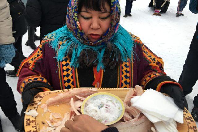 Návštěvníky vítají místní obyvatelé tradiční pochoutkou - stroganinou
