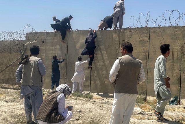 Lidé se snažili dostat na Mezinárodní letiště Hámida Karzaje v Kábulu i přes vysoké zdi | foto: Reuters